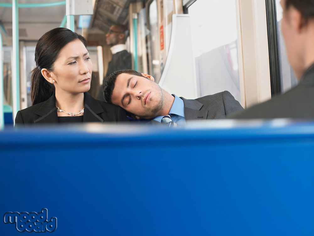Man Sleeping on Businesswoman's Shoulder on Train