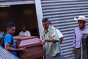 Family members of Yamileth Arteaga Amador, 24, and, Gloria Sinaí Navarro Aguilar, 32, put their coffins onto a truck outside the morgue in Tegucigalpa. The priest from the church the two women attended (wearing the cowboy hat) came to help them. 12th August 2017.
