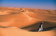 A Bedouin desert guide, Achmed Abu Bakr, strides across a massive dune ridge in the Great Sand Sea, just south of Siwa Oasis in Egypt near Lybia. Also the Egyptian Western Desert or Lybian Desert.
