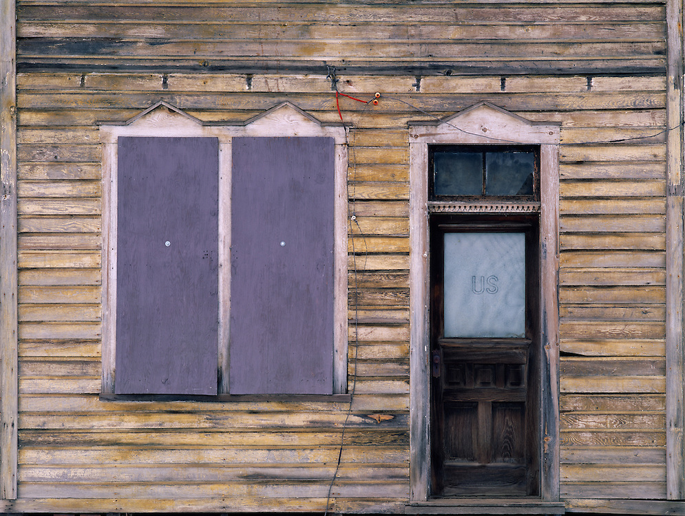 Architectural detail of abandoned home in Mullan, Idaho.  Purple shutters and US etched on door's glass pane.