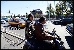 A girl using her iPad on the back of a motorbike in the centre of Beijing, China, Tuesday, 15th October 2013. Picture by Andrew Parsons / i-Images. Picture by Andrew Parsons / i-Images