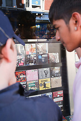 Teenage boys looking at CDs in shop window.