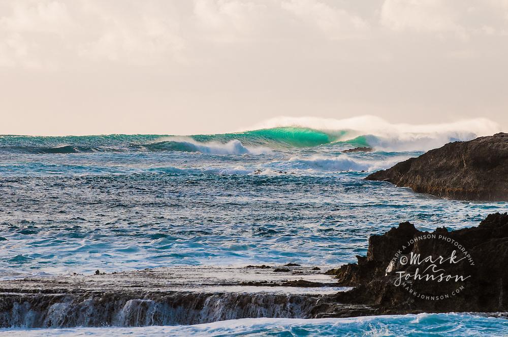 Beautiful backlit green wave breaking onto a lava rock shelf, Oahu, Hawaii