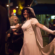 Costumed revelers at annual Greenwich Village Halloween parade, New York, NY; man wearing wedding dress
