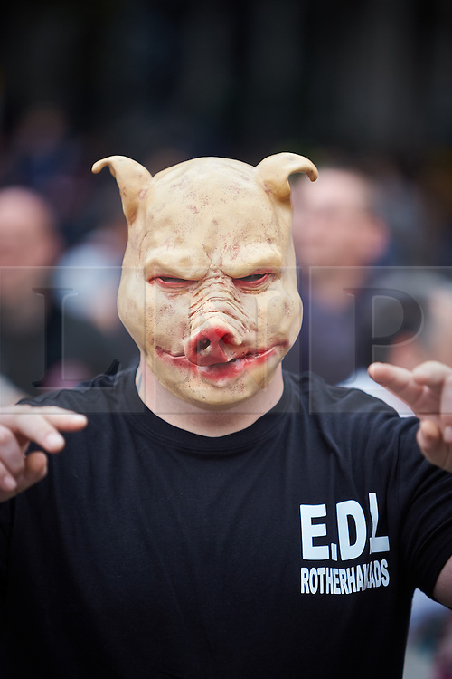 © Licensed to London News Pictures.  20/09/2014. LONDON, UK. A  member of the English Defence League (EDL) pictured wearing a pig mask during a march down Whitehall to Downing Street. The group is attempting to highlight it belief that  Muslim sexual grooming gangs are abusing English girls. Earlier this week a home office official warned of the rise of the far right. Photo credit: Cliff Hide/LNP
