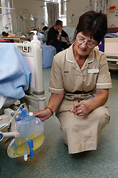 Nursing Auxiliary measuring urine in catheter chamber of patient recovering from hip replacement operation,