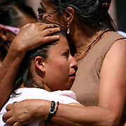 Maria De La Rosa Perez embraces her mother, Maria Luisa Perez, after viewing the statue. The women were on the way to the pharmacy to pick up medication for De La Rosa's son who suffers from leukemia when they saw the statue. They stopped and prayed. The statue was commissioned by the historic Our Lady of Guadalupe church in Santa Fe, New Mexico. The statue was commissioned and funds raised after a controversial state-sponsored art exhibit that pushed the boundaries of the sacred and traditional image of Our Lady of Guadalupe. The statue was loaded onto a flatbed truck and driven north, following El Camino Real, the ancient route the Spanish settlers took north to settle New Mexico and the RIo Grande valley.