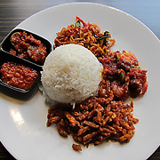 nasi campur (mixed rice) is a popular Indonesian dish of rice accompanied by various vegetables, meat, nuts, tempeh, chili sauce and sometimes fried noodles