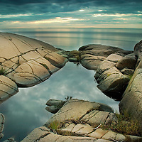 A rocky shore with calm sea and rock pool