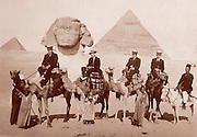 Tourists on camels at the Great Pyramids and Sphinx in Egypt circa 1920