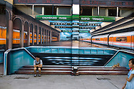 At Pier 2's Arts Plaza, a visitor poses in front of a mural of one of Kaohsiung's MRT stations.