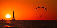 A motorized parachutist gliding over Lake Michigan as the sun sets on a beautiful August evening