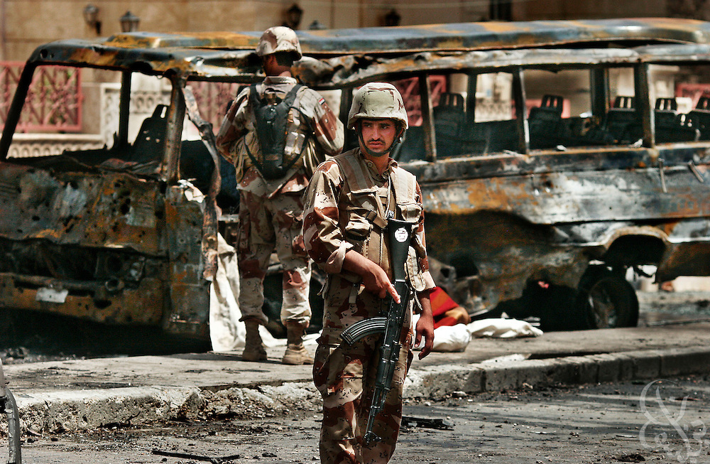 Iraqi Army soldiers guard the scene of a bombing attack that killed 11 people at a police and army checkpoint in central Baghdad, Iraq June 17, 2006. Despite increased security operations designed to curb terrorist violence across the capital, several attacks still occurred on Saturday.
