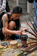 New York, New York. November 1, 2013. Yadira Aleman, 33,  lights incense before the performance. Three members of her dance group, Kalpulli Atl-Tlachinolli performed at a Dia De Los Muertos celebration outside St. Mark's Church in the Bowery. 11012013. Photo by Maya Rajamani/NYCity Photo Wire
