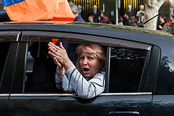 People pile into and onto cars through the city, hanging out their windows and sunroofs chanting, singing, holding flags and peace signs and blowing plastic horns