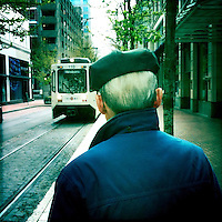 Photos taken with the hipstamatic app on the iPhone. An elderly man, wearing a beret, waits for the light rail, Max train in Downtown Portland, Oregon