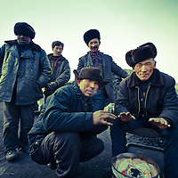 Uyghur coal miners heat themselves in front of a fire in Xinjiang, China, on   February. 17, 2010. Photographer: Bernardo De Niz