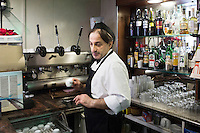 "NAPLES, ITALY - 12 DECEMBER 2014: Ciro Pipolo, a 45 years old barista, serves an espresso coffee at Bar Settebello, a cafe that is part of the ""Rete del Caffè Sospeso"" (Suspended Coffee Network) in Naples, Italy, on December 12th 2014.<br /> <br /> A caffè sospeso,or suspended coffee, is a cup of coffee paid for in advance as an anonymous act of charity. The tradition began in the working-class cafés of Naples, where someone would order a sospeso, paying the price of two coffees but receiving and consuming only one. A poor person enquiring later whether there was a sospeso available would then be served a coffee for free."