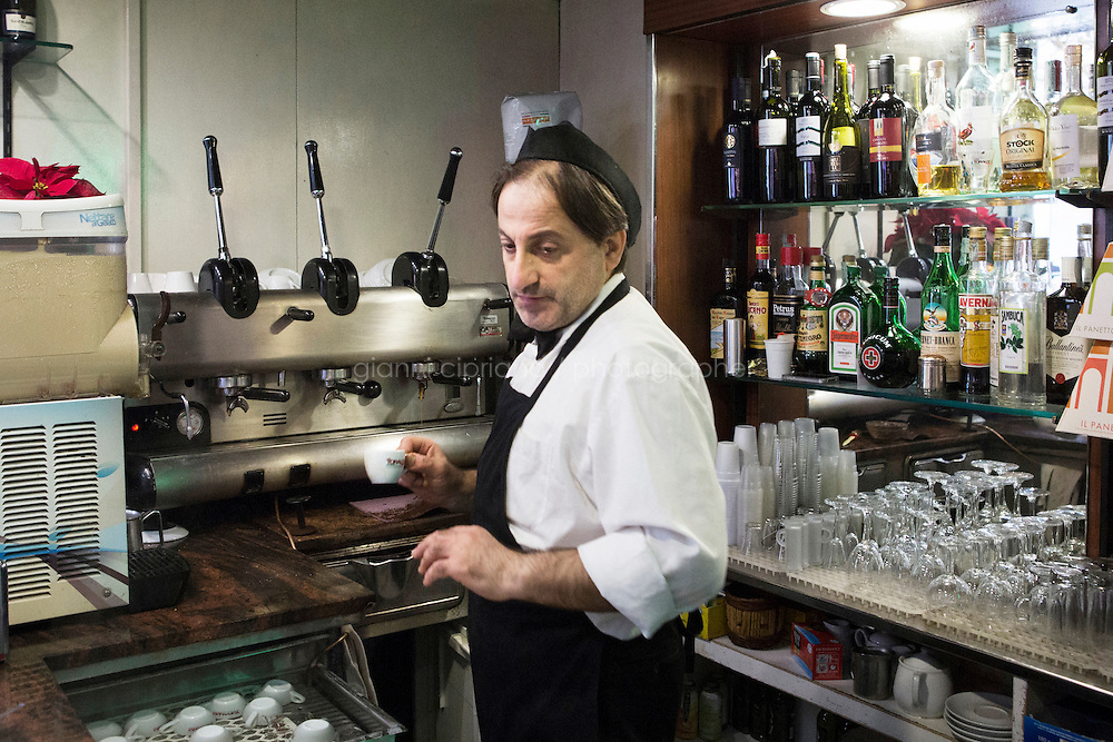 NAPLES, ITALY - 12 DECEMBER 2014: Ciro Pipolo, a 45 years old barista, serves an espresso coffee at Bar Settebello, a cafe that is part of the &quot;Rete del Caff&egrave; Sospeso&quot; (Suspended Coffee Network) in Naples, Italy, on December 12th 2014.<br /> <br /> A caff&egrave; sospeso,or suspended coffee, is a cup of coffee paid for in advance as an anonymous act of charity. The tradition began in the working-class caf&eacute;s of Naples, where someone would order a sospeso, paying the price of two coffees but receiving and consuming only one. A poor person enquiring later whether there was a sospeso available would then be served a coffee for free.