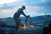 photographer Kawika Singson with his shoes and tripod in flames due to the intense heat of lava.<br />