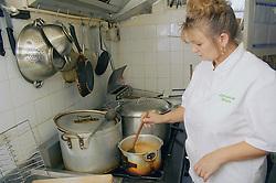 Female chef at work in kitchen preparing food order,