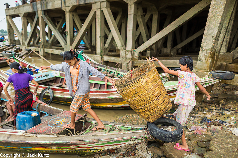 09 JUNE 2014 - YANGON, MYANMAR: Girls board a small boat that takes people across the Yangon River near the San Pya (also spelled Sanpya) fish market. San Pya Fish Market in Yangon is one of the largest wholesale fish markets in Yangon. The market is busiest in early in the morning, from before dawn until about 10AM.    PHOTO BY JACK KURTZ