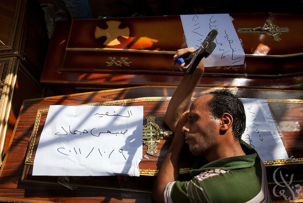 An Egyptian Coptic Christian man mourns over caskets for victims of sectarian violence October 10, 20011 at the Coptic Hospital in Cairo, Egypt. At least 26 people, mostly Christian, were killed during sectarian clashes that saw the worst violence since the Revolution that toppled former Egyptian president Hosni Mubarak earlier this year. Egyptian Coptic Christians make up about 10% of Egypt's 80 million population and periodically violence flares between the Christian minority and the majority Muslim population. (Photo by Scott Nelson)
