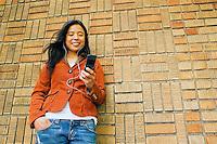 Early 30's Asian (Japanese/Filipino) woman standing in front of a brick wall text messaging with her cell phone and listening to music with her ipod..Model Release: 20070513_MR_A