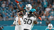 Aug 22, 2019; Miami Gardens, FL USA;  Jacksonville Jaguars quarterback Nick Foles (7) looks to pass while  offensive guard A.J. Cann (60) blocks Miami Dolphins linebacker Nate Orchard (4) who tries to swat down the pass during an NFL preseason game at Hard Rock Stadium. The Dolphins beat the Jaguars 22-7. (Kim Hukari/Image of Sport)