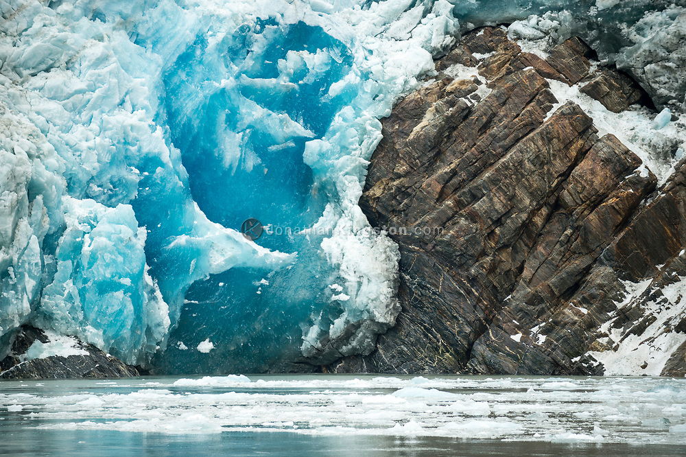 Close up of blue glacial ice against rock at South Sawyer Glacier, Tracy Arm fjord, Alaska.