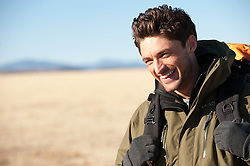 Portrait of a young man smiling while enjoying a backpacking hike