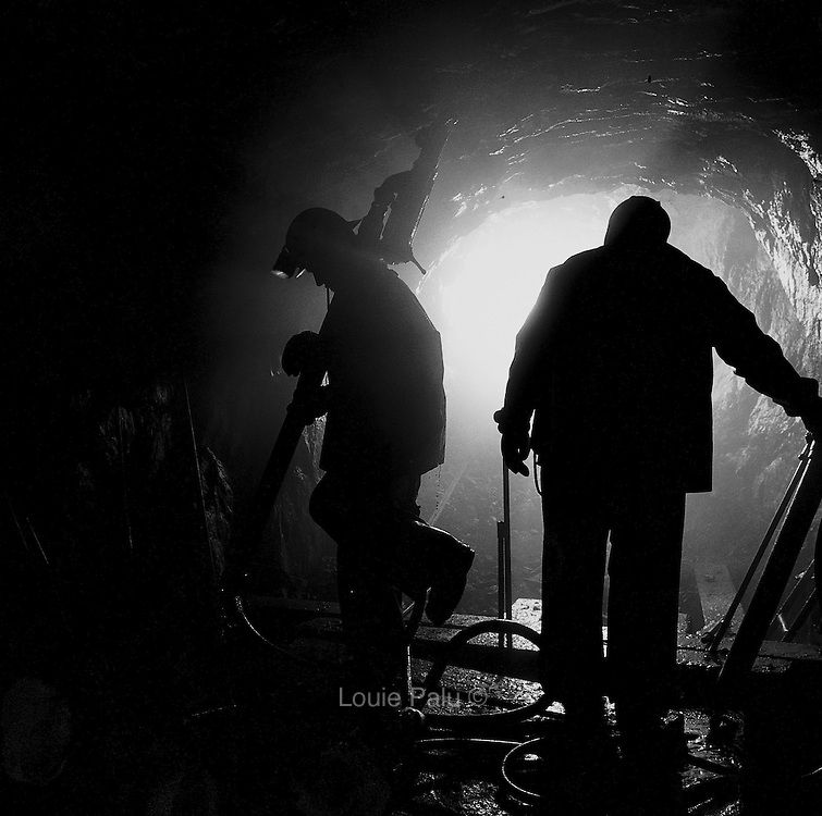 Miners moving jackleg drills and gear before blasting in a shrinkage stope, 700 foot level, Cheminis Mine, Larder Lake, Ontario. From the book Cage Call: Life and Death in the Hard Rock Mining Belt. An in-depth project spanning over 12-years examining communities in one of the richest mining regions in the world located in Northwestern Ontario and Northeastern Quebec in Canada.
