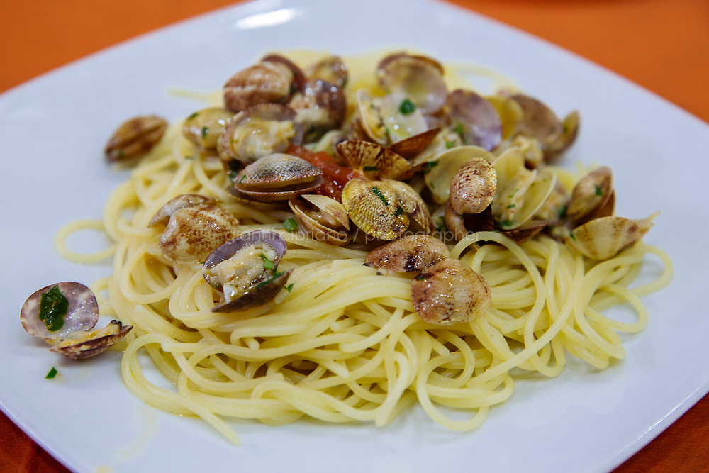 NAPLES, ITALY - 20 MARCH 2018: A dish of spaghetti with clams is seen here at the Pizzeria e Trattoria Vigliena in Naples, Italy, on March 20th 2018.<br /> <br /> Pizzeria e Trattoria Vigliena is a restaurant outside of the city center and adjacent to the port. At lunch, the place is packed with workers from the docks and ship owners and workers from the recently built Marina Vigliena.<br /> <br /> The restaurant is owned by Raffaele Esposito, Concetta&rsquo;s son and the third generation of a family of chefs who founded this restaurant in the middle of the 20th century