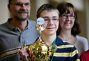 Kyle Schroeder, a 14-year-old student from St. Brendon School, poses with a picture in front of his parents and other family (not pictured) after being announced the Columbus Metro Regional Spelling Bee winner, Saturday, March 16, 2013. Schroeder and Matthew Pitcock, the Southeastern Ohio region spelling bee winner, will be attending the Scripps National Spelling Bee held near Washington, D.C from May 28-30, 2013.
