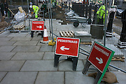 Three pedestrian signs show differing directions for passers-by in London's Cannon Street during pavement refurbishment.