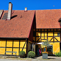 Hedman Courtyard and Yellow House in Malmö, Sweden <br /> The Hedmanska Gården façade facing the Lilla Torg square is historically impressive. This is one of five buildings from the Hedmanska Farm. It was first mentioned in a 1529 written record. Some people believe the family farm may have started in the 1400s. Don't miss the opportunity to walk through the short tunnel to see this inner Hedman courtyard. It is named after Gabriel Hedman. He used this yellow, half-timbered building for grain storage starting in 1855.