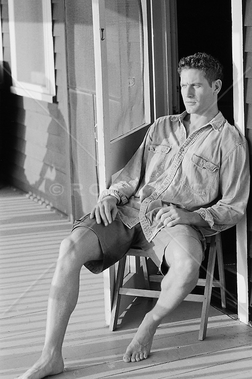 Man seated in a doorway at a lakehouse