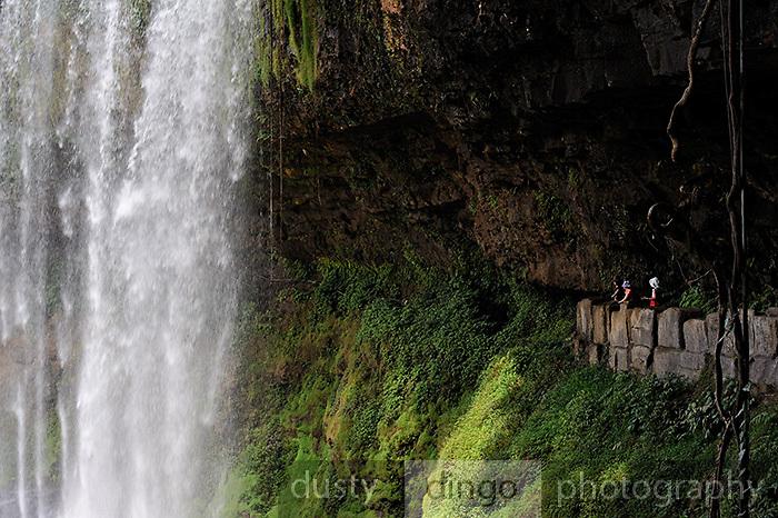 People on path leading to very edge of waterfall. Dam Bri waterfall, Da Lat, Vietnam