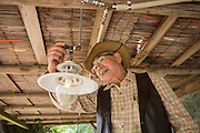 Tadao Yuge turns on a gas lamp that is powered by his biogas made from cow manure.