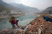 Liuku, Yunnan, China - 17 JAN 2006 - A Chinese woman picks through garbage on the banks of the Nu Jiang River. A leaked Chinese government report, recently cleared it to press ahead with the main parts of a plan to build a cascade of 13 dams and power stations down the gorges that line the Nu River, in the mountains where Burma, Tibet and the Chinese province of Yunnan meet. In the past five years, the startling growth of China's economy has put pressure on both its water supplies - 90 per cent of the country's cities are fed by contaminated rivers - and its energy resources.