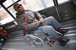 Visually-impaired wheelchair user with white stick on transport resource for people with physical and sensory impairment.