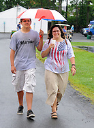 Tyler Van Valkenburg (left) and Kelly Van Valkenburg share an umbrella and walk through the park during Quakertown Community Day at Memorial Park Saturday July 4, 2015 in Quakertown, Pennsylvania. (Photo by William Thomas Cain)