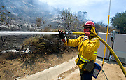 July 13, 2015 - Yorba Linda, CA, USA - <br /> <br /> water planes take to the sky to help put out fires<br /> <br /> An OCFA firefighter sprays water on a hot spot near the side of Santiago Canyon Road as a vegetation fire that grew to burn more than 100 acres Monday morning, threatened some structures near Irvine Lake and caused officials to close down Santiago Canyon Road in unincorporated Orange County, California<br /> ©Exclusivepix Media