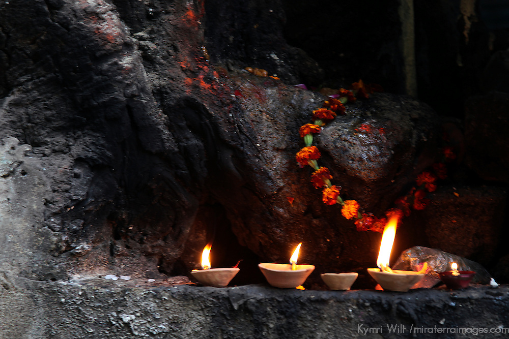 Asia, India, Varanasi. Candles and marigolds drape a small hindu shrine in the old city of Varanasi.
