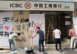 Kowloon, Hong Kong, China,. 7 October, 2019. After a night of violent confrontations between police and pro-democracy protestors in MongKok and YauMaTei in Kowloon, many MTR railway stations and what are thought to be pro-Beijing business franchises were vandalised. Removing graffiti and repairs to Chinese ICBC Bank .