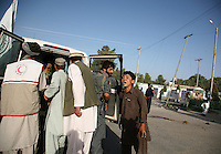 A young boy wails as medics place another boy, believed to be his brother, inside an ambulance after they were hit by a rocket aimed at a polling station in Lashkar Gah on the day of the Afghan presidential elections.