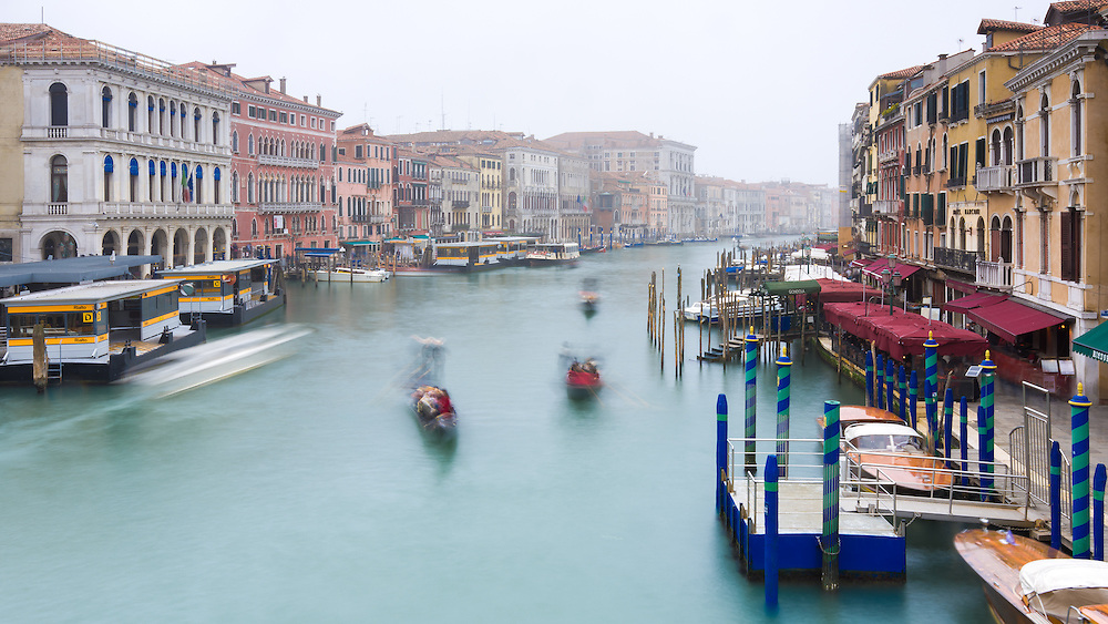 The view from Rialto Bridge in Venice along the grand canal on a misty morning with boats and gondolas blurred to show movement