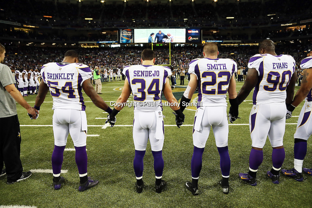 A group of Minnesota Vikings players joins hands in memory of the victims lost in the Sandy Hook Elementary School tragedy before the NFL week 15 football game against the St. Louis Rams on Sunday, Dec. 16, 2012 in St. Louis. The Vikings won the game 36-22. ©Paul Anthony Spinelli