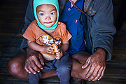 Portrait of a child belonging to the Mishmi tribe sits in the lap of his father with an orange in his hand in Hunli village, Arunachal Pradesh