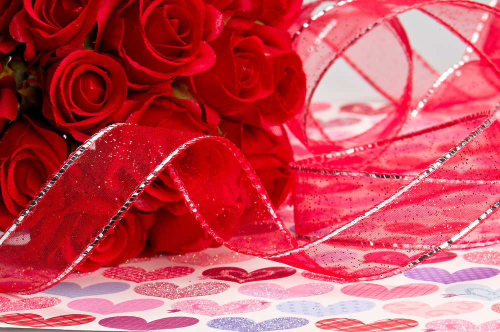 Close up of red roses and red ribbon for Valentines Day.